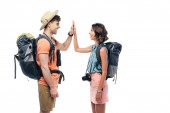 two cheerful tourists with backpacks giving high five isolated on white