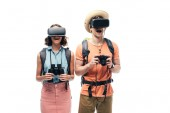 two cheerful tourists with binoculars and digital camera using virtual reality headsets isolated on white