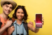 Fotografie selective focus of cheerful young woman standing near smiling boyfriend and showing smartphone with trading courses app on yellow background