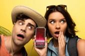 shocked young woman showing smartphone with trading courses app while standing near surprised man on yellow background