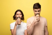 positive man and woman looking at each other while drinking coffee to go on yellow background