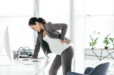 pregnant woman enduring pain and leaning on table