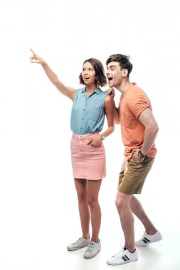 smiling woman pointing with finger and looking away with excited man on white background