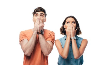 shocked man and woman looking up and covering faces with hands isolated on white