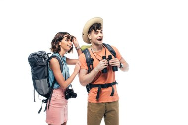 two excited young tourists with binoculars and digital camera looking away isolated on white