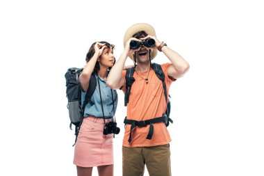 Excited tourist looking in binoculars near cheerful young woman isolated on white stock vector