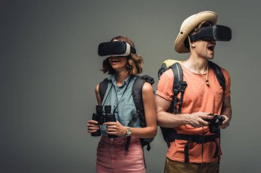 two excited tourists with binoculars and digital camera using virtual reality headsets on grey background