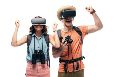 two cheerful tourists showing yes gestures while using virtual reality headsets isolated on white