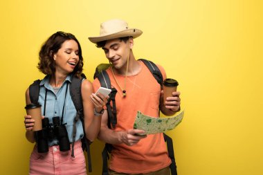 cheerful woman showing smartphone to man with geographic map on yellow background