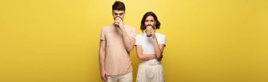 panoramic shot of young man and woman drinking coffee to go while looking at camera on yellow background