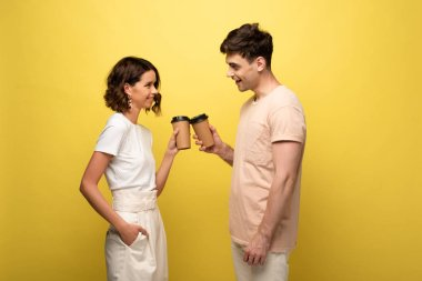 cheerful man and woman clinking with paper cups while looking at each other on yellow background