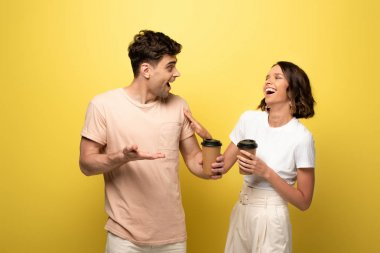 Excited man and woman talking while holding coffee to go on yellow background stock vector
