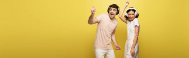 panoramic shot of excited man and woman dancing while listening music in headphones on yellow background