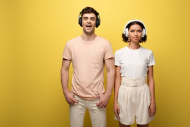 cheerful man and woman posing at camera while listening misic in headphones on yellow background