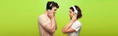 panoramic shot of positive man and woman in headphones listening music with closed eyes on green background