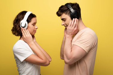 young man and woman in headphones listening music with closed eyes on yellow background