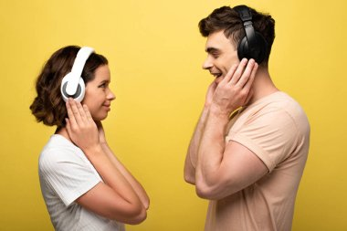 cheerful man and woman listening music in headphones while looking at each other on yellow background