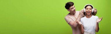 panoramic shot of handsome man putting on headphones on cheerful girl on green background