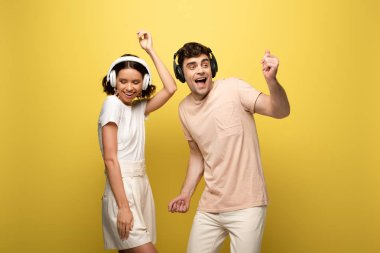 excited man and woman dancing while listening music in headphones on yellow background