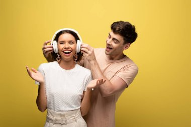handsome man putting on headphones on cheerful girl on yellow background