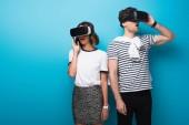 fiatal, divatos férfi és nő használ virtuális valóság fejhallgatók kék háttér