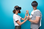 cheerful man and woman holding hands while using virtual reality headsets on blue background