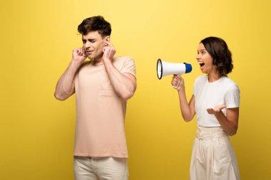 Irritated girl quarreling in loudspeaker at boyfriend on yellow background stock vector