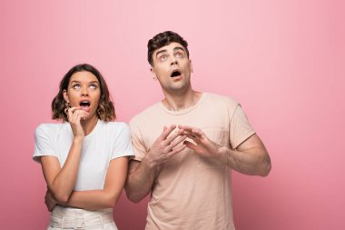 surprised man and woman gesturing while looking up on pink background