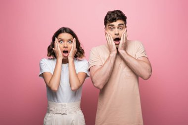 shocked man and woman holding hands near face while looking at camera on pink background