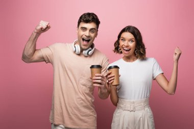 cheerful man and woman showing yes gestures while holding paper cups and looking at camera on pink background