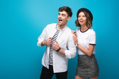 young, trendy man and woman smiling and looking away on blue background