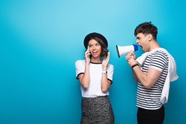 irritated man quarreling in loudspeaker at girlfriend talking on smartphone on blue background