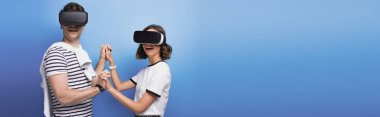 panoramic shot of young man and woman holding hands while using virtual reality headsets on blue background