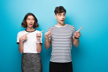cheerful man and woman looking away and pointing with fingers on blue background