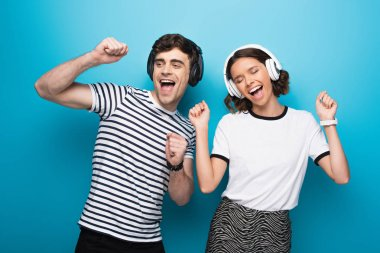 excited man and woman dancing while listening music in headphones on blue background