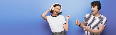 panoramic shot of excited man and woman dancing while listening music in headphones on blue background