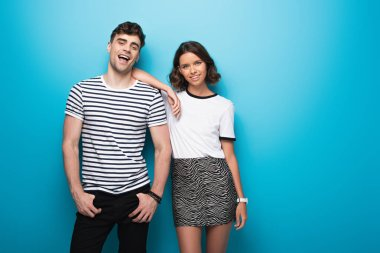 happy, trendy man and woman smiling at camera on blue background