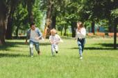 šťastná rodina v příležitostném oblečení v parku během dne