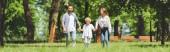 pohled na rodinné příslušníky držící ruce a běh v parku během dne