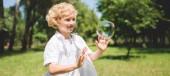 panoramatický záběr roztomilý chlapec gestikulovat blízko mýdlové bubliny v parku