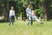 family spending time together, father spinning son in park