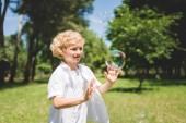 rozkošný chlapec gestikulovat blízko mýdlové bubliny v parku
