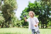 rozkošný chlapec foukající v parku mýdlové bubliny