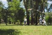 eccitato famiglia in esecuzione e giocare con aquilone volante in parco