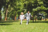 father and adorable son playing football with soccer ball in park