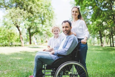 happy mother and son with disabled father on wheelchair in park