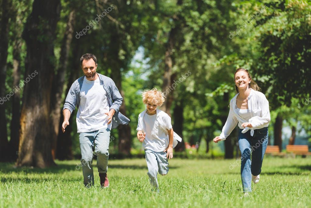 happy family running in park during daytime and looking at camera