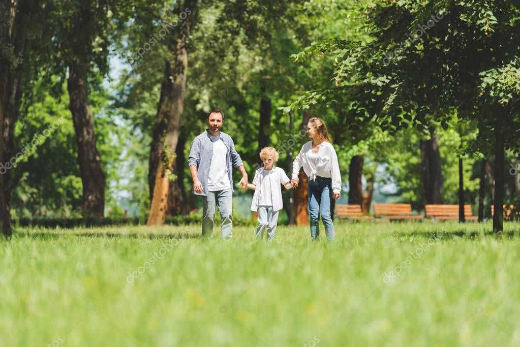 selective focus of happy family holding hands and running in park during daytime