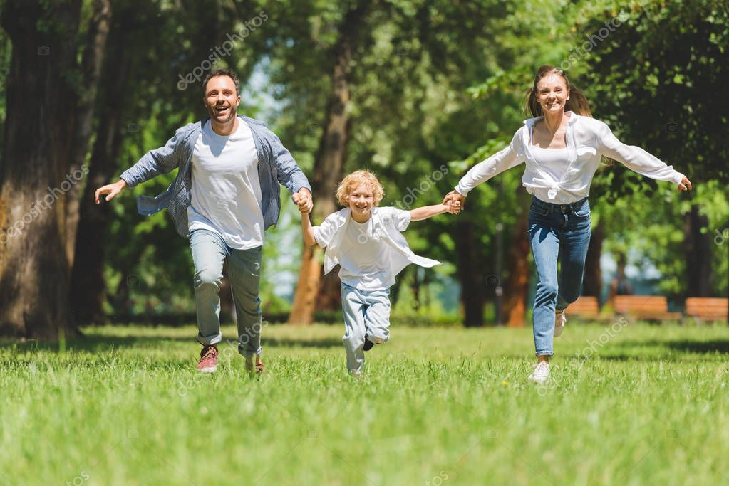 smiling family holding hands and running in park during daytime