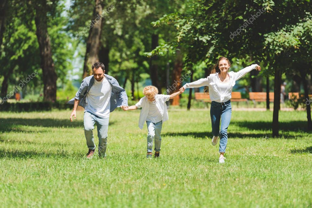 excited family holding hands and running in park during daytime